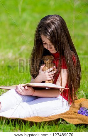 Adorable girl in summer park reading book. Adorable girl in summer park reading book