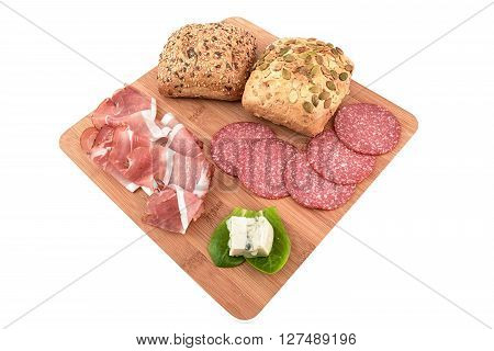 cereal bread, speck, salami and gorgonzola on chopping board