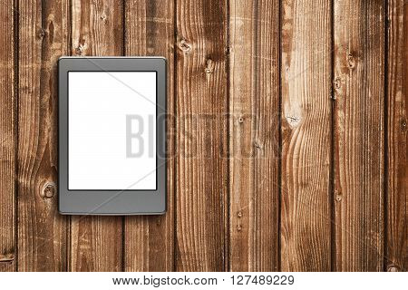 E-book reader on wooden table top view