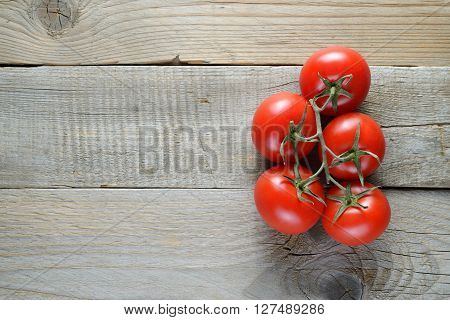 Tomatoes on old wooden background top view