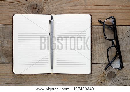 Open diary with pen and glasses on wooden table