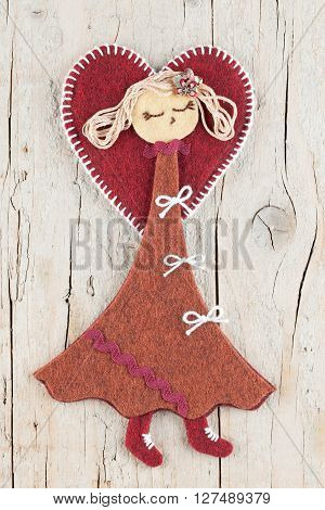 Sewn handmade angel doll on wooden background