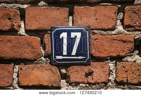 Weathered grunge square metal enameled plate of number of street address with number 17 closeup