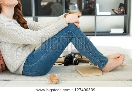 Close up of girl thinking. Happy young woman day dreaming at home. Young photographer munching biscuits and cookies.