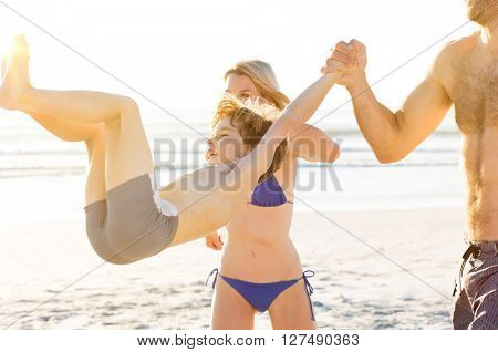 Father and mother playing with son on the beach. Cute happy family enjoying at the beach. Child jumping with parents at seaside.