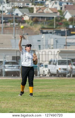 Softball outfielder following through on her throw