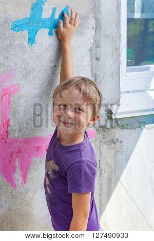 Young boy drawing with paints on the wall