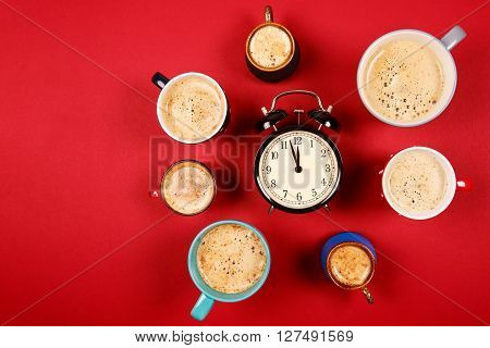 Many different cups of coffee and cappuccino and big alarm clock on red background. Too much caffeine in one day