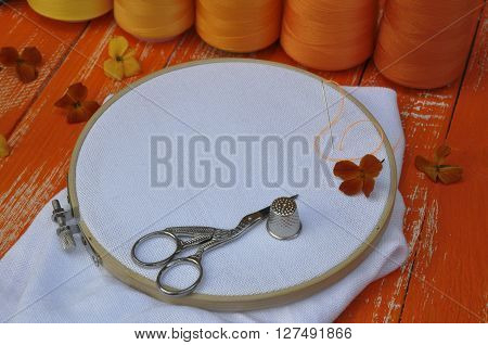 Hoop thread and fabrics for sewing and needlework on a background thread orange tone