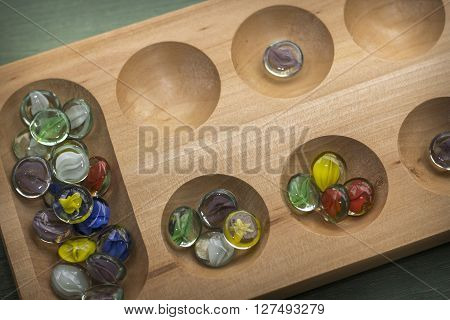 Traditional Mancala boardgame with glass pieces on wooden table