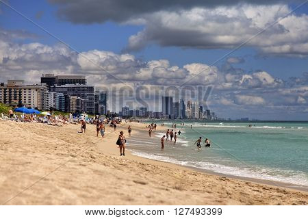 Miami Beach USA - May 5 2013: Scene of the crowded beach. People having fun sunbathing and swimming in the shallow water. Skyline in the back.
