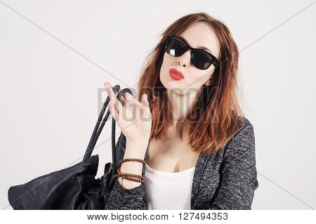 Fashion young trendy model in nice clothes posing in the studio. Wearing sunglasses and handbag at workplace office background