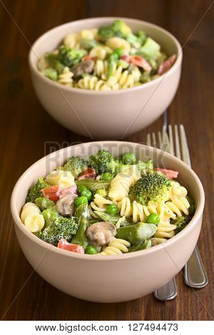 Pasta primavera with green asparagus pea broccoli mushroom and tomato in cream sauce served in two bowls photographed on dark wood with natural light (Selective Focus Focus in the middle of the first bowl)