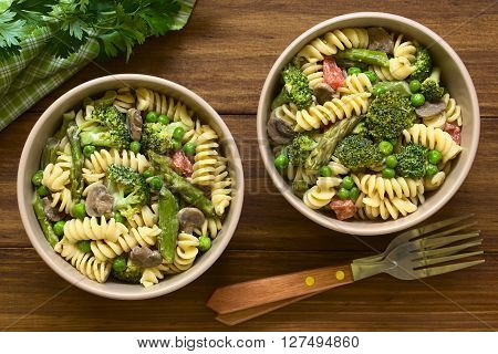 Pasta primavera with green asparagus pea broccoli mushroom and tomato in cream sauce served in bowls photographed overhead on dark wood with natural light