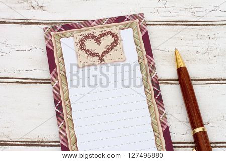 Blank notepad and paper A notepad and pen on weathered wood background with copy-space