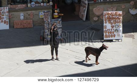 AREZZO ITALY - CIRCA APRIL 2015: unidentified girl with a dog taking a picture on the main square