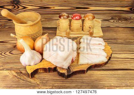 Piece and sliced fresh raw pork lard on wooden board mortar garlic onion on the table