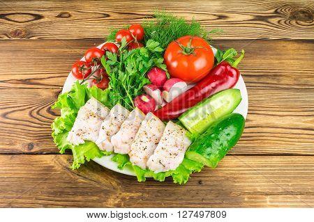 Plate with sliced fresh pork lard fresh produce vegetables on the wooden table
