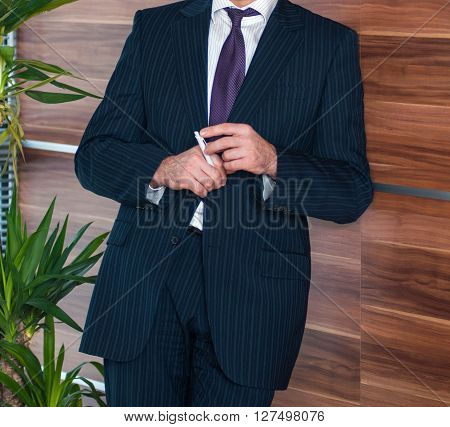 Confident businessman executive portrait holding white pen in hands lying next to luxury wooden wall in his modern office