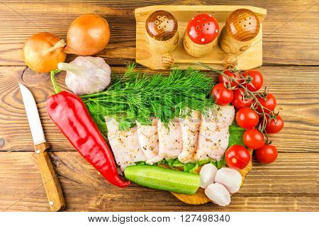 Sliced fresh pork lard fresh produce greens vegetables on the wooden board and knife on table top view