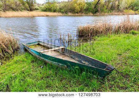 old wooden boat near river bank