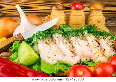 Sliced fresh pork lard fresh produce greens vegetables on the wooden board and knife on table selective focus