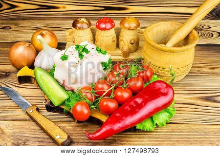 Piece of fresh pork lard fresh produce greens vegetables on the wooden board and knife on table