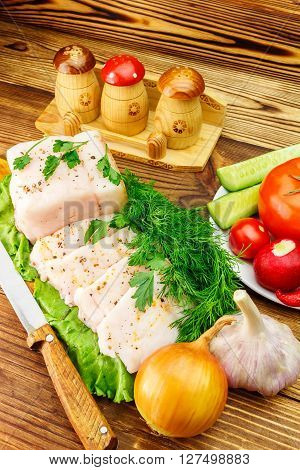 Piece and sliced fresh pork lard fresh produce greens vegetables on the wooden board and knife on table
