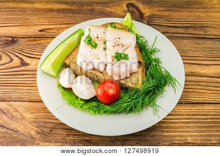 Sandwich with slice of rye bread fresh pork lard and parsley fresh produce tomato in the plate on wooden table