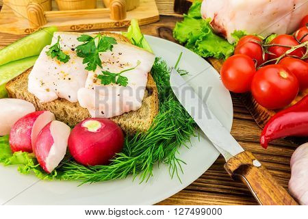 Sandwich with slice of rye bread fresh pork lard and parsley in the plate fresh produce greens vegetables on wooden table.