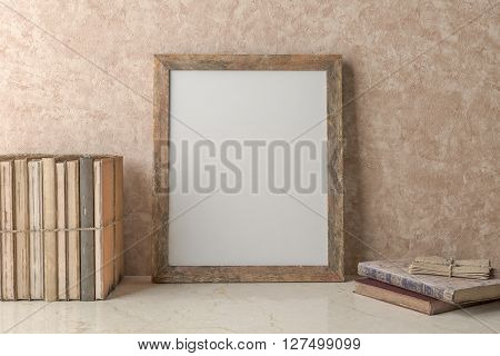 Blank Picture frame on the wall and old books