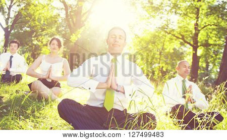 Business people meditating in the woods.