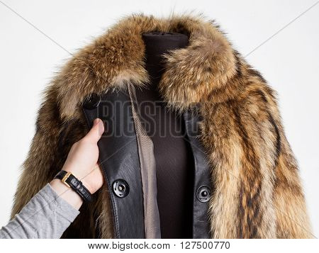 Man's hand touching a fur coat white background