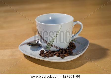 An empty cup on a saucer with a spoon is standing on a table. On the saucer are lying some coffee beans.