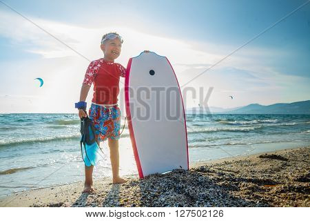 Happy Surfing boy on a beach ready to go into the water. Sunset time.