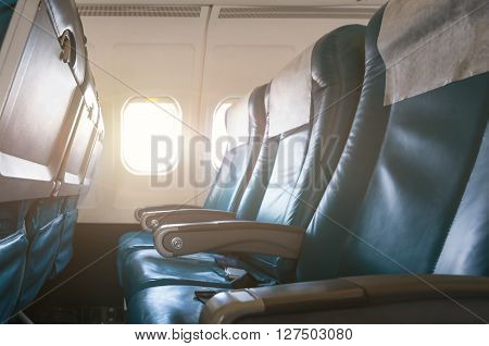 Interior of airplane with empty seats and sunlight at the window. Travel concept. ** Note: Shallow depth of field