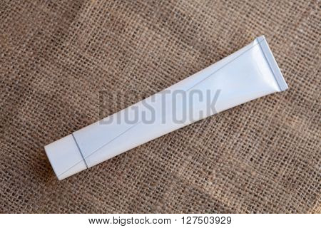 White, empty and clean tube, ready for your design product, on hessian fabric