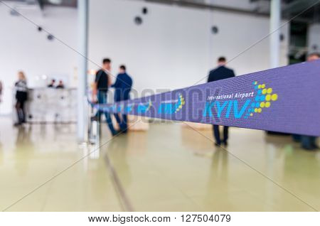 KYIV, UKRAINE - APRIL, 07, 2016: Kyiv International Airport, Zhuliany. Stop line or ribbon with logo of airport Kyiv with blurred people.