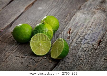 Close-up of fresh bright limes on wooden background
