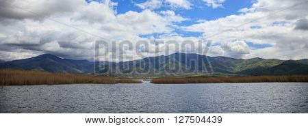Idyllic scene of white clouds above mountain landscape and water