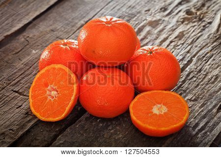 Close-up of several halved and whole mandarines on wooden table