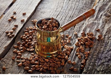 Close-up of golden cezve full of coffee beans on wooden table