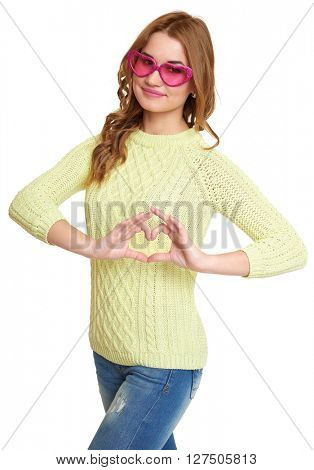 girl in big pink eyeglasses make hearts shape gesture, dressed jeans and a green sweater posing in studio on white background
