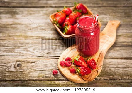 Fresh red berry smoothie on wooden table
