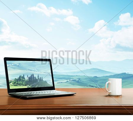 notebook and cup on table, tuscany, Italy as background