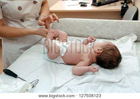 Pediatrician examining littlle newborn baby on the table