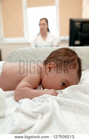 Little newborn baby lying on the table in doctor's  office