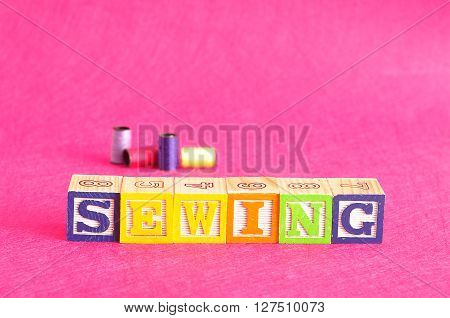 The word sewing spelled with colorful alphabet blocks displayed with spools of thread that is out of focus against a pink background