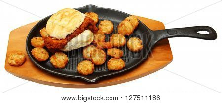 Spicy Chicken Biscuit and Hashbrowns on Skillet isolated over white