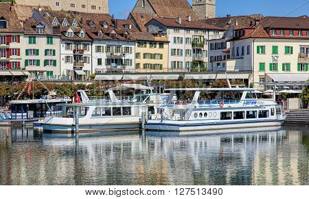 Rapperswil, Switzerland - 8 September, 2015: boats at pier on Seequai quay with old town buildings in the background. Rapperswil is a part of the municipality of Rapperswil-Jona in the Swiss canton of St. Gallen.